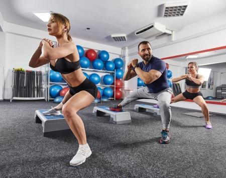 Photo pour Instructeur de conditionnement physique et les filles font d'entraînement cardio avec steppers - image libre de droit