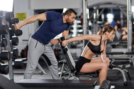 Personal trainer helping woman with triceps workout in the gym