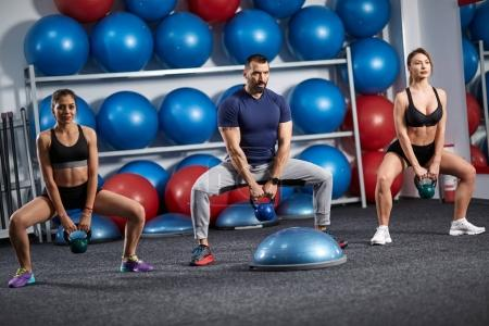 Fitness instructor with two girls working out with kettlebell