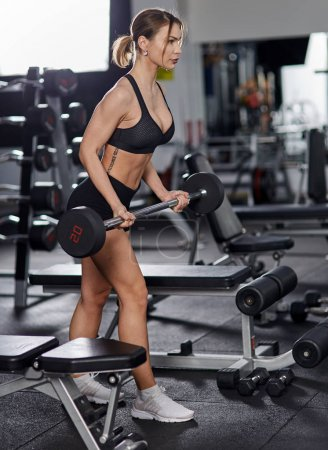 Young woman in the gym doing biceps curll with barbell