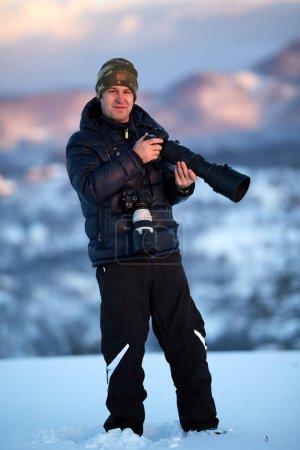 Photographer with two cameras shooting landscapes at sunset
