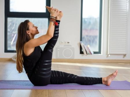 Young woman yoga teacher in her studio taking various poses by the window