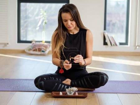 Yoga trainer meditating and doing sage smoke ritual