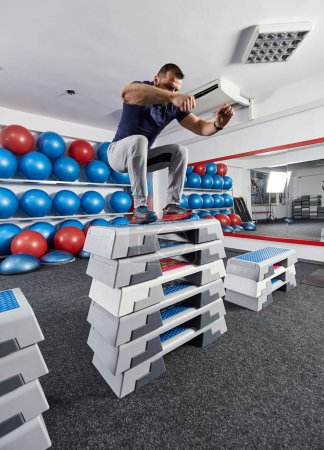 Athletic man jumping on many stacked steppers