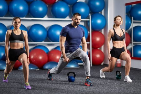 Fitness instructor and girls doing lunges in the gym