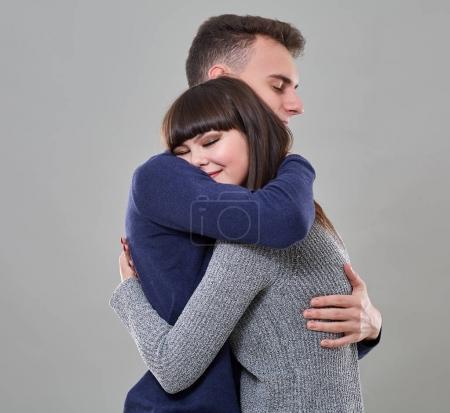 Photo pour Couple d'adolescents embrassant sur fond gris - image libre de droit