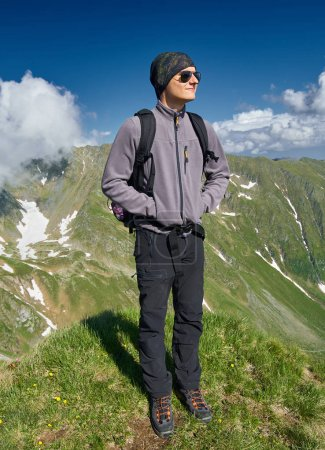 Young backpacker hiking into the mountains.
