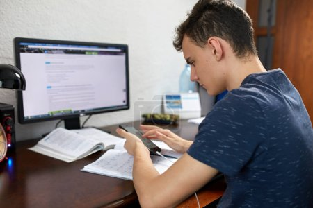 Student diligently doing homework at desk with computer