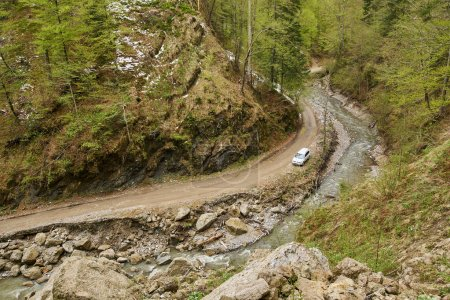 Aerial shot of an offroad car on muddy road in mountains