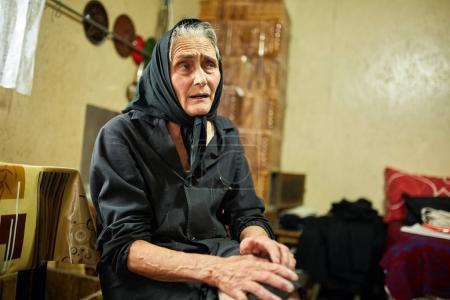 Closeup of sad old woman indoor