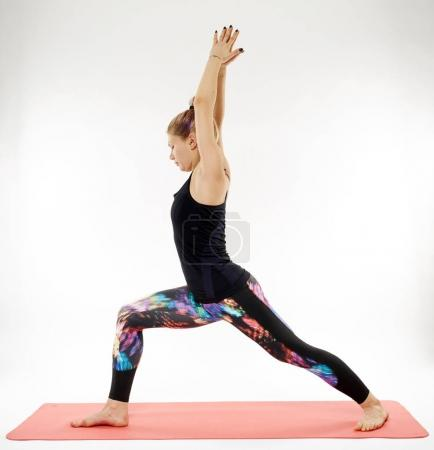 Young woman yoga practitioner exercising on rubber mat isolated on white background
