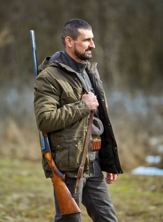 Hunter with double barrel gun on shoulder standing in forest