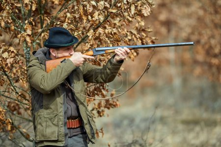Hunter with double barrel gun standing in forest and aiming at wild animals