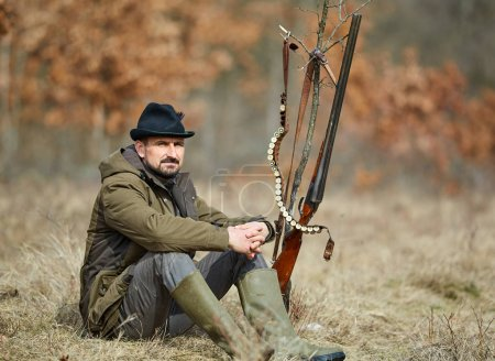 Hunter with double barrel gun resting in forest