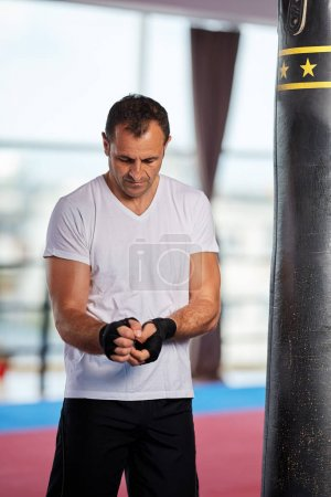 Photo for Kickbox fighter training with heavy bag in the gym - Royalty Free Image