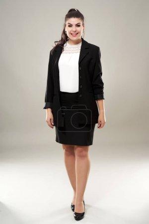 Confident hispanic businesswoman full length on gray background