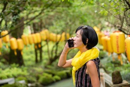 Photo pour Mature asiatique femme parler sur cellulaire à temple - image libre de droit