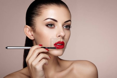 Photo for Beautiful woman paints lips with lipstick. Beautiful woman face. Makeup detail. Beauty girl with perfect skin. Red lips and nails manicure - Royalty Free Image