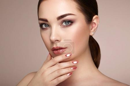 Photo for Beauty brunette woman with perfect makeup. Red lips and nails. Perfect eyebrows. Skin care foundation. Beauty girls face isolated on beige background. Fashion photo - Royalty Free Image
