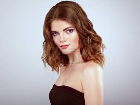 Foto de Mujer morena con el pelo ondulado brillante largo y volumen. Preciosa modelo con peinado rizado. Maquillaje perfecto. Modelo de belleza estilo - Imagen libre de derechos