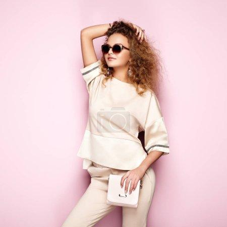 Foto de Retrato de moda de mujer en traje de verano. Chica posando sobre fondo rosa. Bolso rosa y gafas de sol. Peinado rizado con estilo. Lady glamour - Imagen libre de derechos