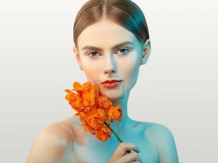 Photo pour Portrait de belle jeune femme avec orchidée. Femme brune avec maquillage de luxe. Une peau parfaite. Des cils. Fard à paupières cosmétique. Fleurs orange - image libre de droit