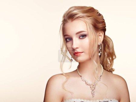 Foto de Chica rubia con pelo rizado largo y brillante. Hermosa modelo mujer con peinado rizado. Productos de cuidado y belleza de pelo. Joyería y maquillaje perfecto - Imagen libre de derechos
