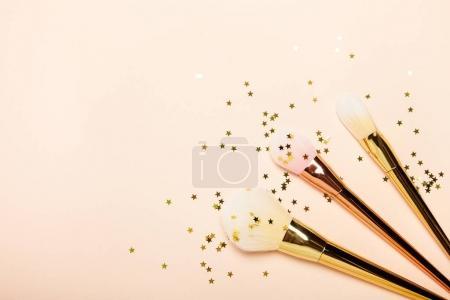 Photo pour Cosmétiques et accessoires pour femmes à la mode. Falt Lay. Étoiles d'or. Pinceaux de maquillage. Accessoires de maquillage sur fond beige - image libre de droit