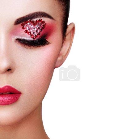 Photo pour Visage de belle femme avec coeur de maquillage de vacances. Maquillage de Saint Valentin. Lèvres rouge à lèvres rose. Détail de maquillage. Visage de jeune fille sur fond blanc - image libre de droit