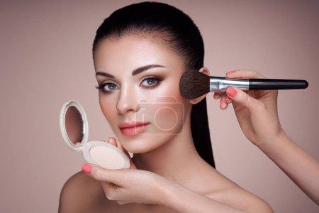 Photo pour Belle femme s'applique la tonicité de la peau avec une brosse. Beau visage de femme. Maquillage parfait. Fondation des soins de la peau. Artiste de maquillage pinceaux - image libre de droit