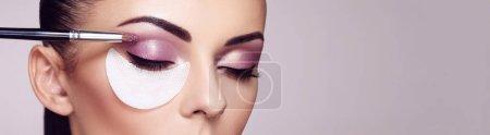 Photo pour Maquilleuse applique le fard à paupières. Visage de belle femme. Maquillage parfait. Détail de maquillage. Fille de beauté avec une peau parfaite. Ongles et manucure - image libre de droit