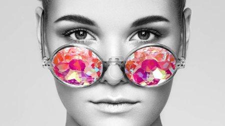 Photo pour Verticale de belle jeune femme avec des glaces colorées. Mode beauté. Maquillage parfait. Décoration colorée. Lunettes de soleil holographiques. Couleur de corail - image libre de droit