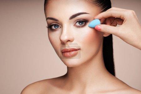 Photo pour Maquilleuse applique skintone. Visage de belle femme. Maquillage parfait. Fondation des soins de la peau. Artiste maquilleur éponge - image libre de droit