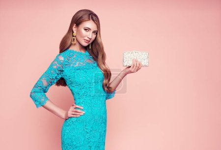 Blonde young woman in elegant turquoise dress. Model posing on a pink background. Jewelry and hairstyle. Girl with handbag. Fashion photo. Spring summer lookbook