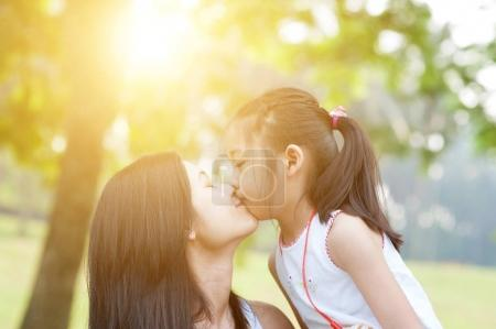 Mother and daughter kissing.