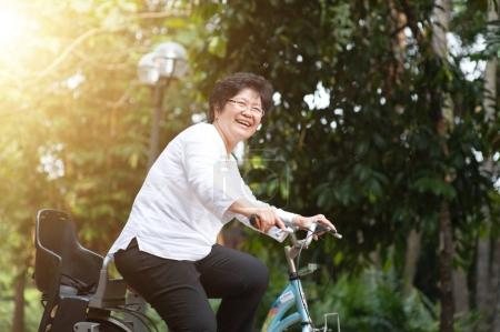 Photo for Active elderly Asian woman cycling, senior adult activity, riding bike outdoor in morning. - Royalty Free Image
