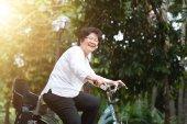 Elderly Asian woman biking