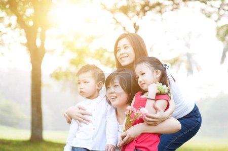 Photo pour Famille asiatique au parc, les parents et les enfants, plein air matin avec flare soleil. - image libre de droit