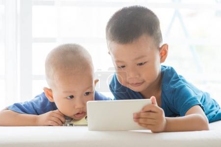 Foto de Niños adictos al gadget de tecnología. Chicos asiaticos jugando con el teléfono inteligente en el hogar - Imagen libre de derechos