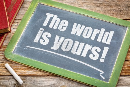 Photo for The world is yours - a positive affirmation. White chalk text on a blackboard with books. - Royalty Free Image