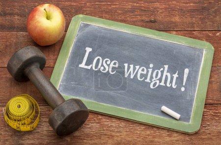 Photo pour Concept de perte de poids - panneau de tableau noir en ardoise contre le bois de grange peint en rouge avec haltère, pomme et ruban à mesurer - image libre de droit