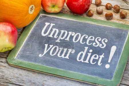 Photo for Unprocess your diet - healthy eating concept - white chalk text on blackboard with fruits and nuts - Royalty Free Image