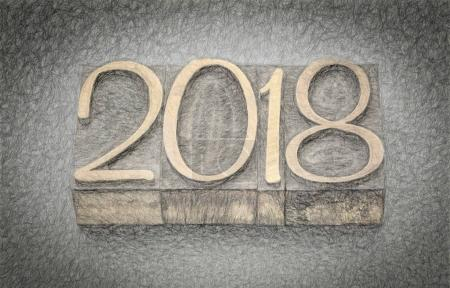 Photo for 2018 year in letterpress wood type blocks against gray slate stone, digital charcoal painting effect - Royalty Free Image