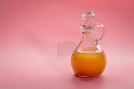 Photo pour Vinaigre de cidre de pomme cru non filtré avec mère - une béquille en verre sur fond rose - image libre de droit