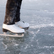 Young woman ice skating outdoors on a pond on a fr...