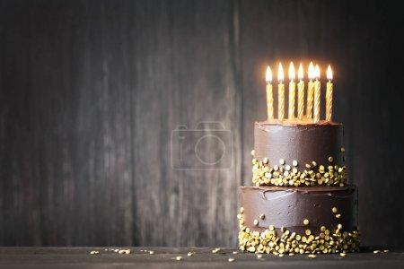 Foto de Pastel de chocolate de cumpleaños con velas de oro - Imagen libre de derechos
