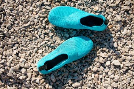 Photo pour Chaussures d'eau bleue sur la plage de galets - image libre de droit