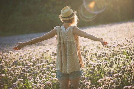 Young woman relaxing in summer sunset outdoor. People freedom style. Open arms.