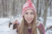Winter portrait of young beautiful blonde woman wearing knitted hat. Snowing winter beauty fashion concept. Snowy forest on background.