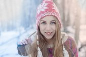 Colourful filtered image.  Winter portrait of young beautiful blonde woman wearing knitted hat. Snowing winter beauty fashion concept. Snowy forest on background.